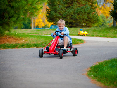 Image of a boy driving a red pedal car