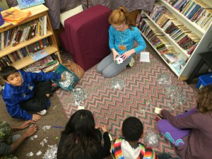 Elementary students in classroom sorting pop tabs