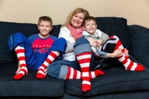 Photo of Kirsten and her two children in red and white striped socks