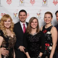 Group of three women and three men standing in front of RMHC backdrop. Dressed in fancy clothing for the Sweetheart Ball.