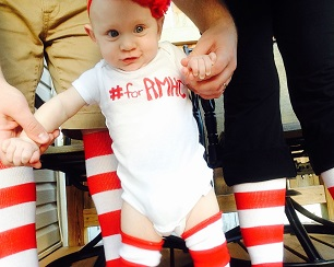 Baby wearing red and white striped socks and #forRMHC onesie