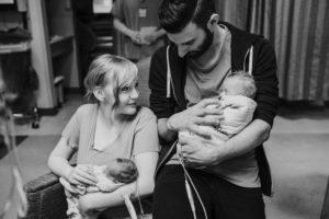 Mom and Dad holding twin baby girls, black and white photograph
