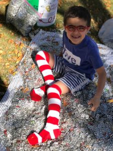William wearing his striped socks surrounded by pop tabs